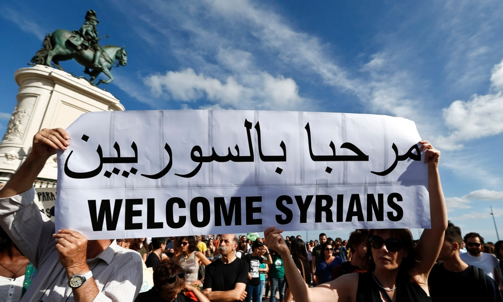 People take part in a demonstration in support of migrants holding up placards saying ' Syrians Refugees welcome' in LIsbon, Portugal, 12 September 2015. ANTÓNIO COTRIM/LUSA
